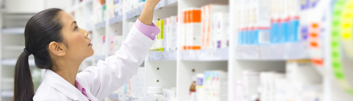 A pharmacy technician, selecting a prescription off the shelf.