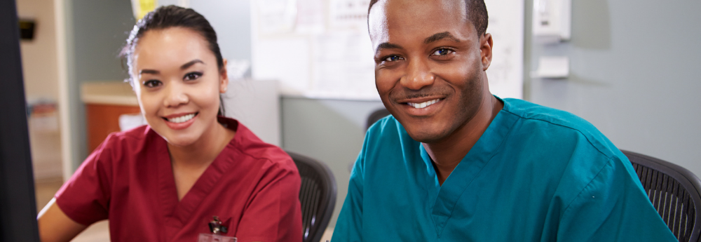 Two medical students sitting down in chairs with scrubs on.