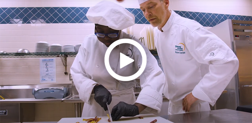 Video play button, with a culinary arts student in training taking instructions from their teacher.