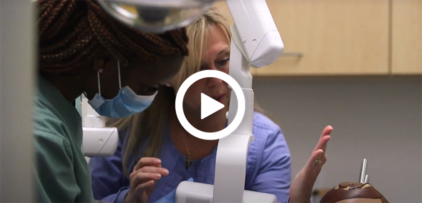 Video play button with Instructor teaching students in the Dental Assistant Training program at Dorsey College