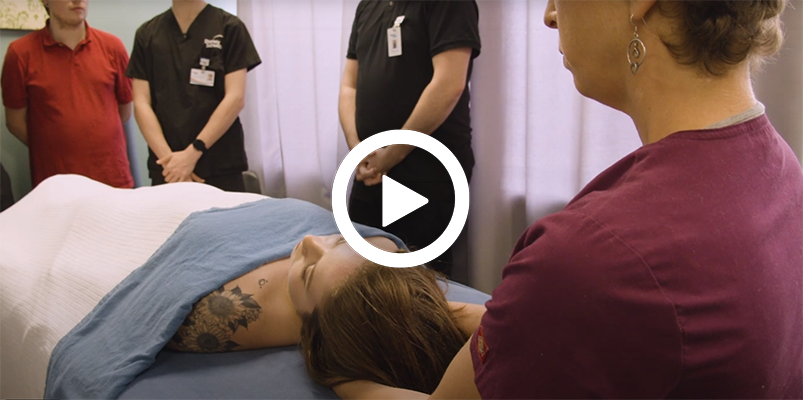 Video play button with a massage therapy training instructor and students.