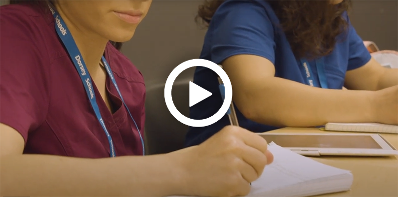 Video play button with students taking down notes in medical billing and coding classes.