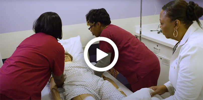 Video play button, with a patient care technician, training students on a dummy.